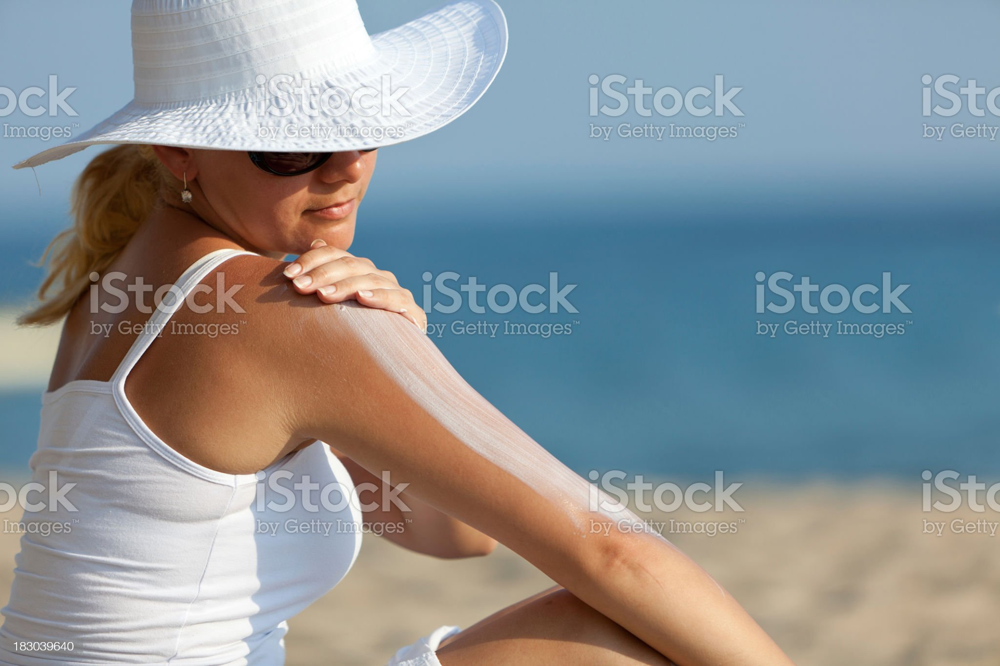 Woman applying Suntan Lotion at the beach royalty-free stock photo