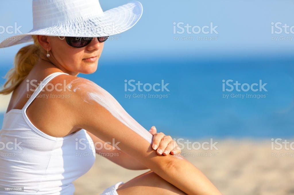 Woman applying Suntan Lotion at the beach stock photo