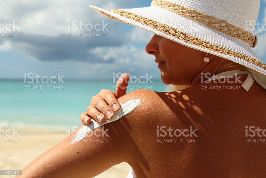 Woman applying Suntan Lotion at the beach stock photo