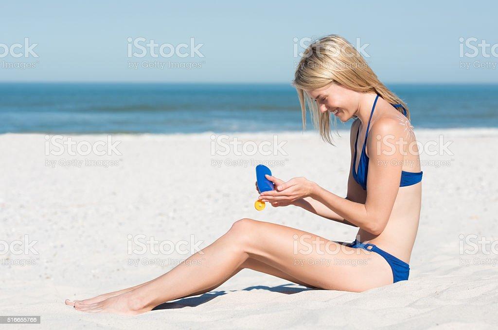 Woman applying suntan lotion stock photo