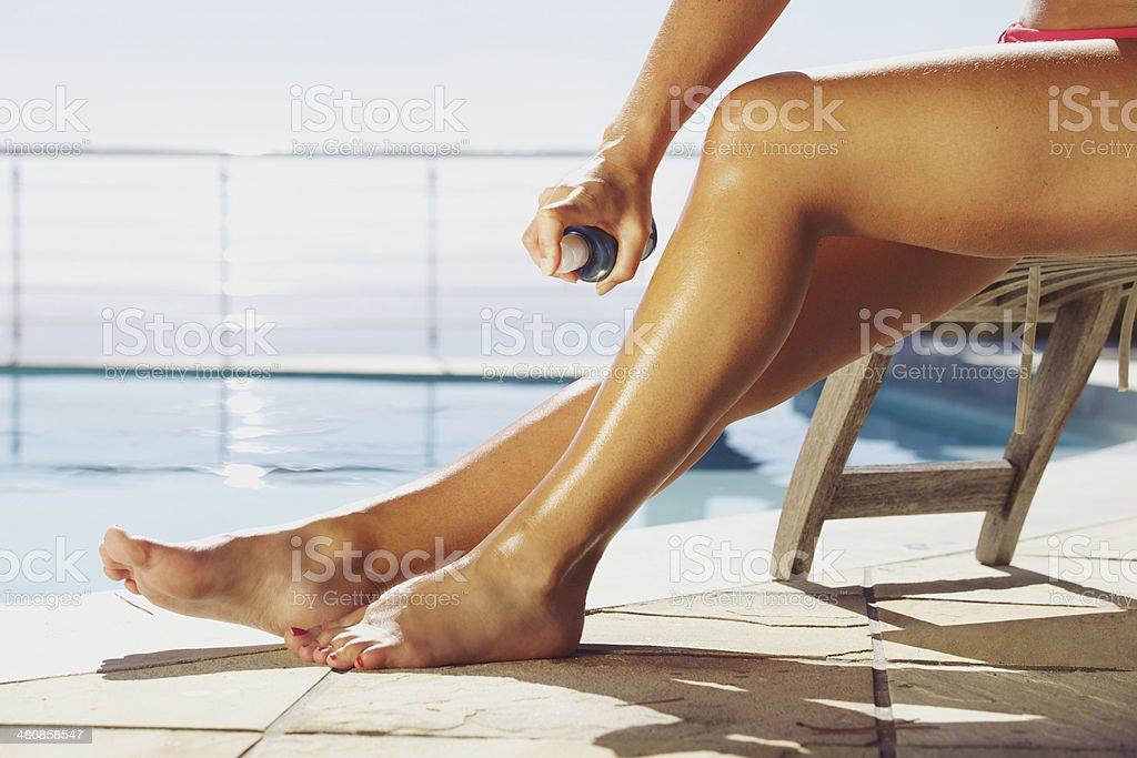 Woman applying suntan spray on her legs stock photo