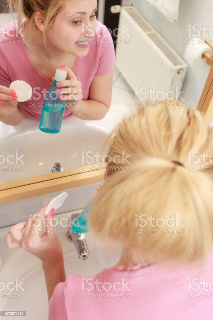 Woman applying tonic on cotton pad stock photo