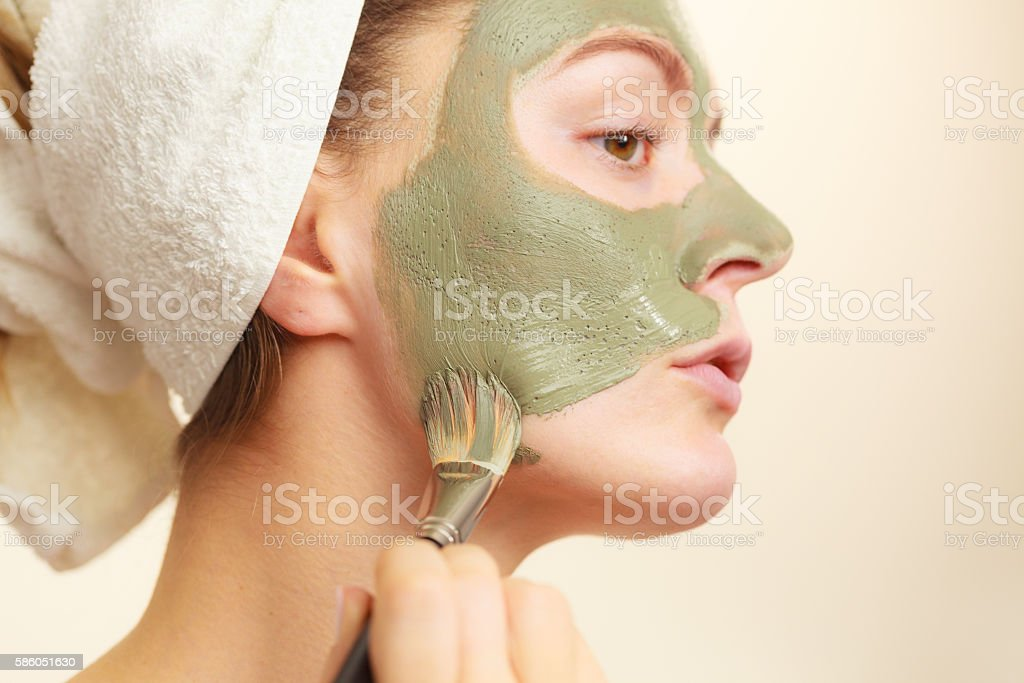 Woman applying with brush clay mud mask to her face stock photo