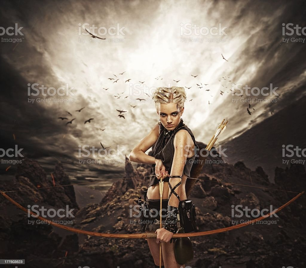 Woman archer against storm over rocks stock photo