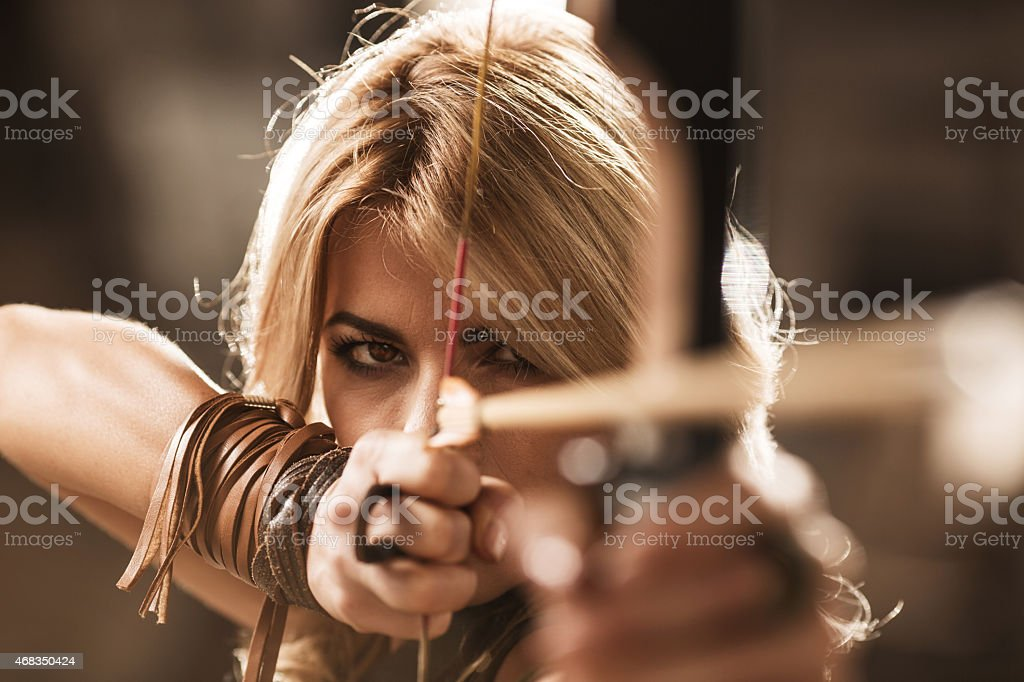 Woman archer aiming with bow and arrow. stock photo