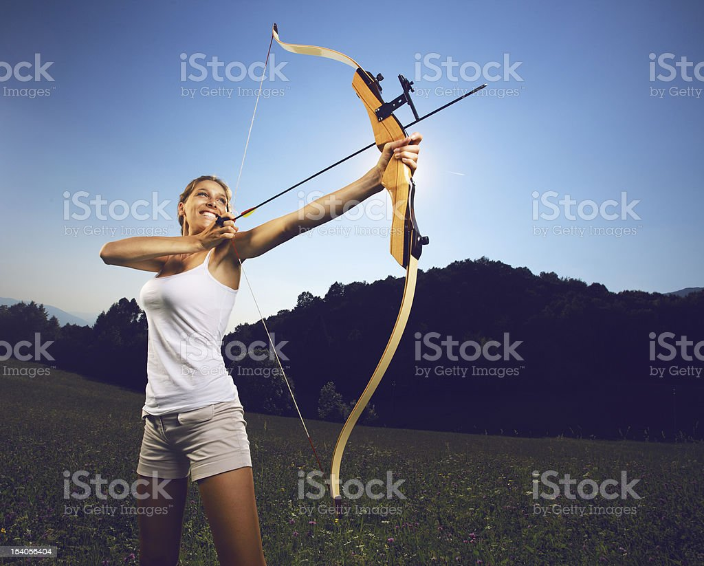 Woman archer holding a bow and arrow stock photo