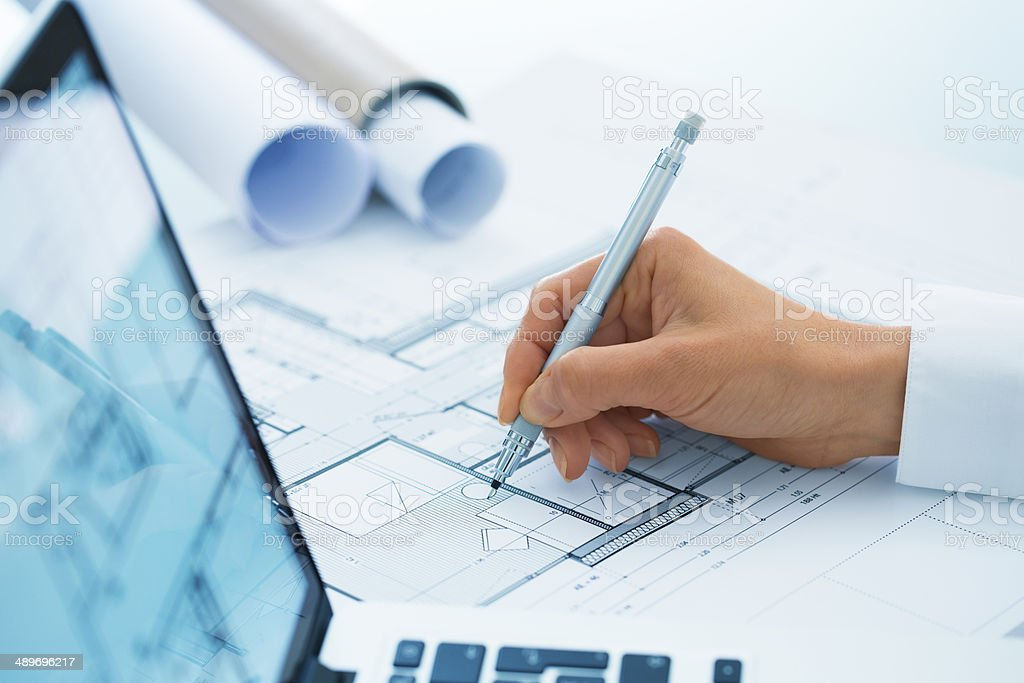 Woman Architect drawing on blueprints construction project stock photo