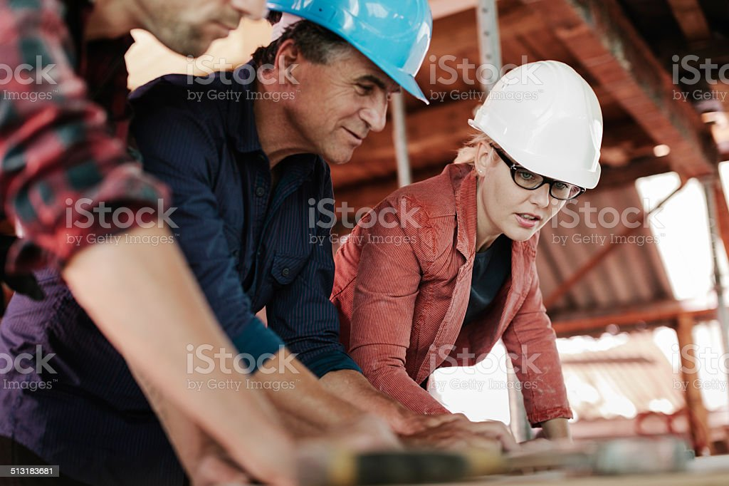 Woman Architect lookng over building Plans stock photo