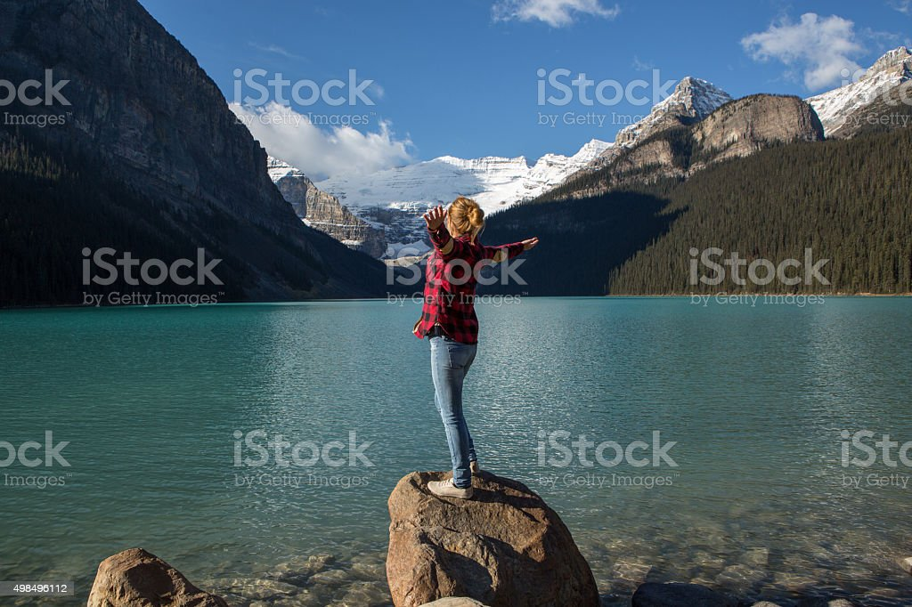 Woman arms outstretched at lake Louise stock photo