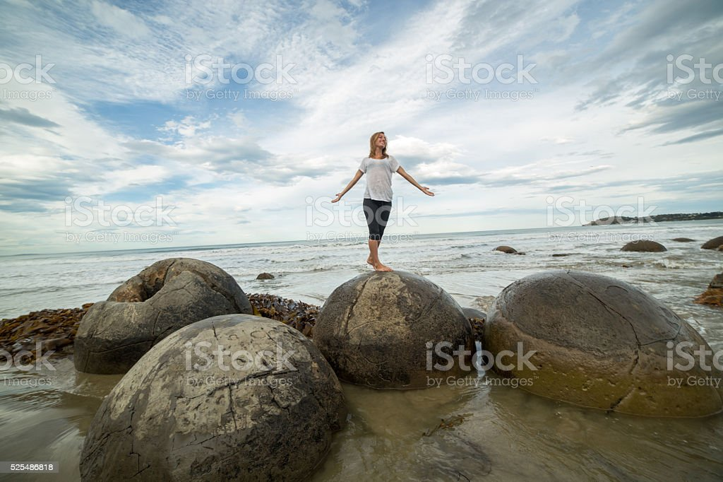 Woman arms outstretched on spheric boulder by the sea stock photo