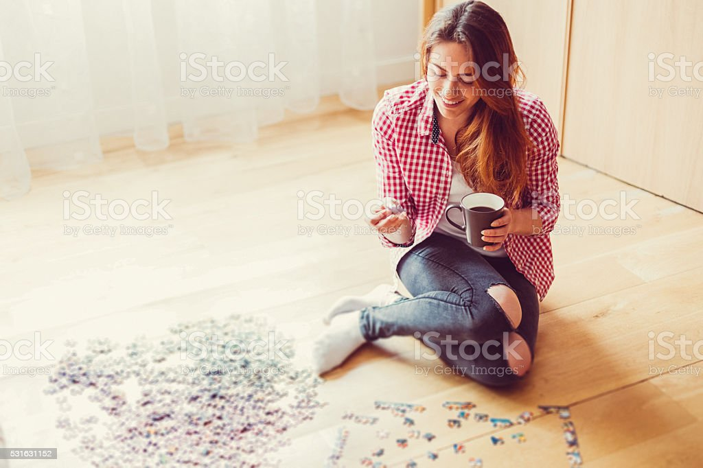 Woman arranging jigsaw puzzle at home stock photo