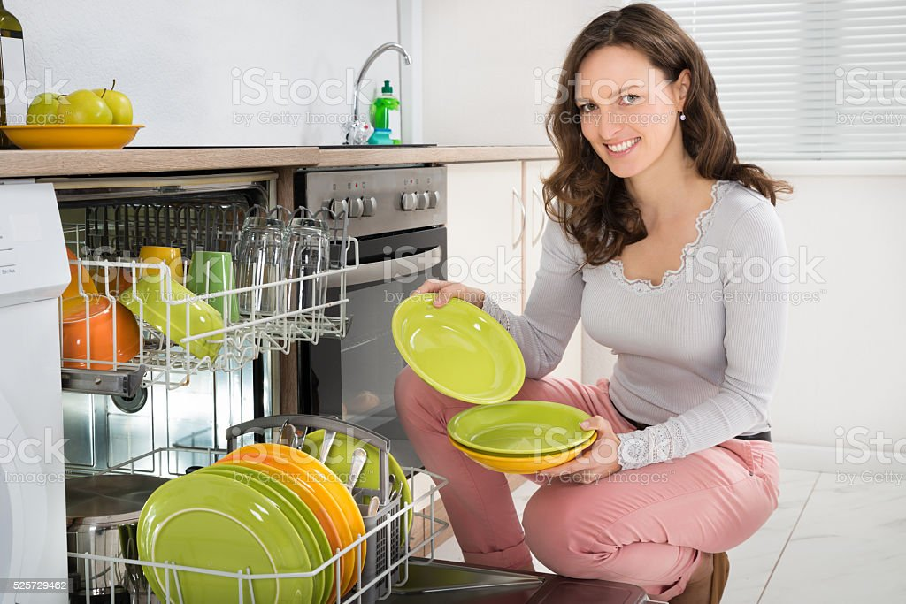 Woman Arranging Plates In Dishwasher stock photo