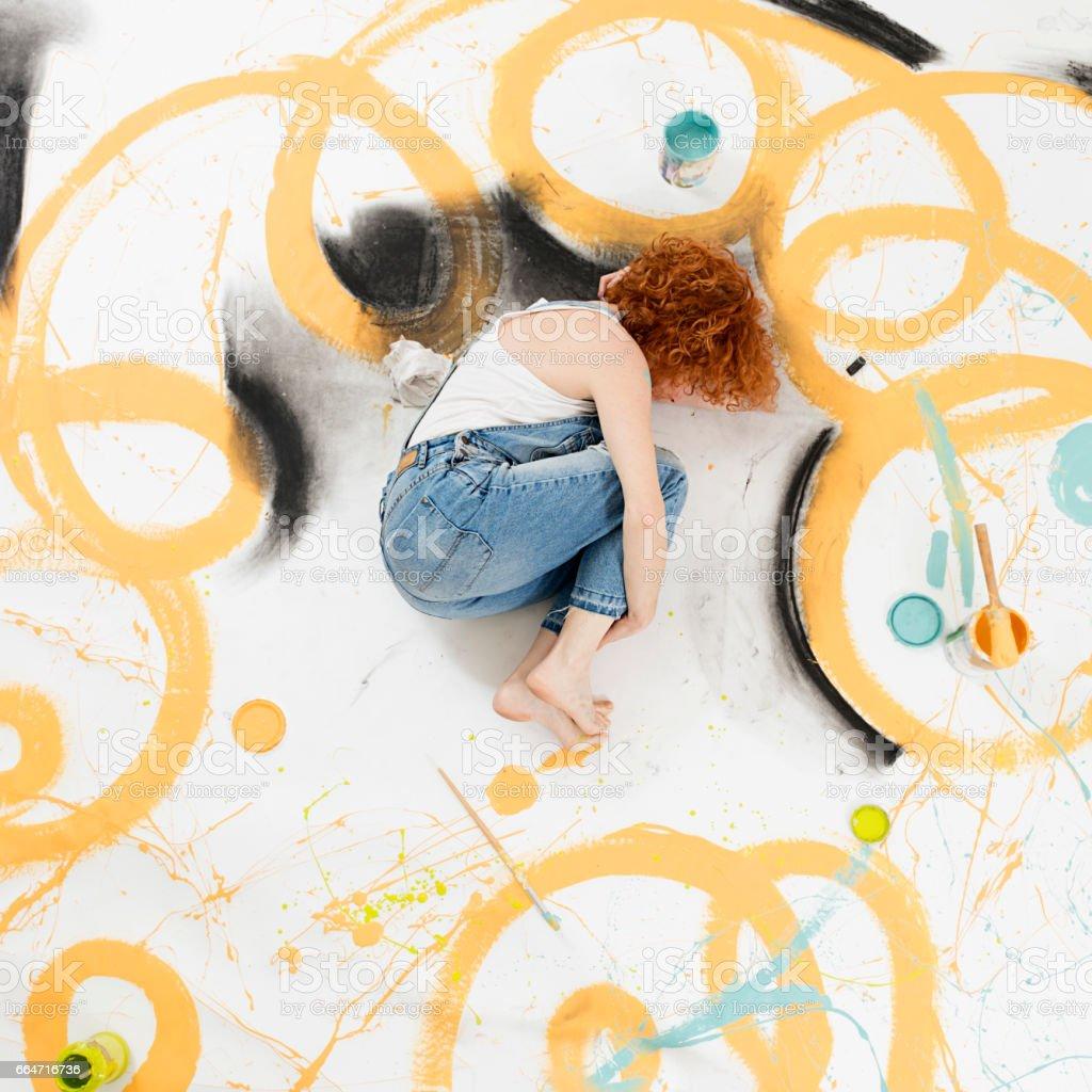 woman artist painting on the floor stock photo