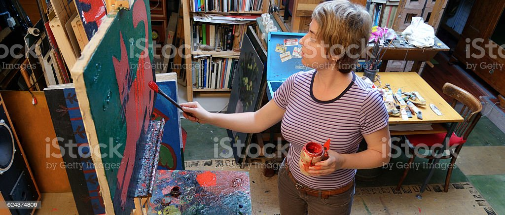 Woman artist paints in her workshop. stock photo