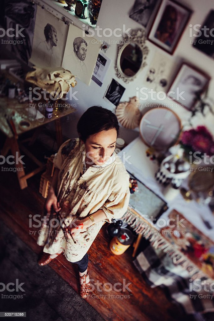 Woman artist thinking in her art studio wearing a smock stock photo