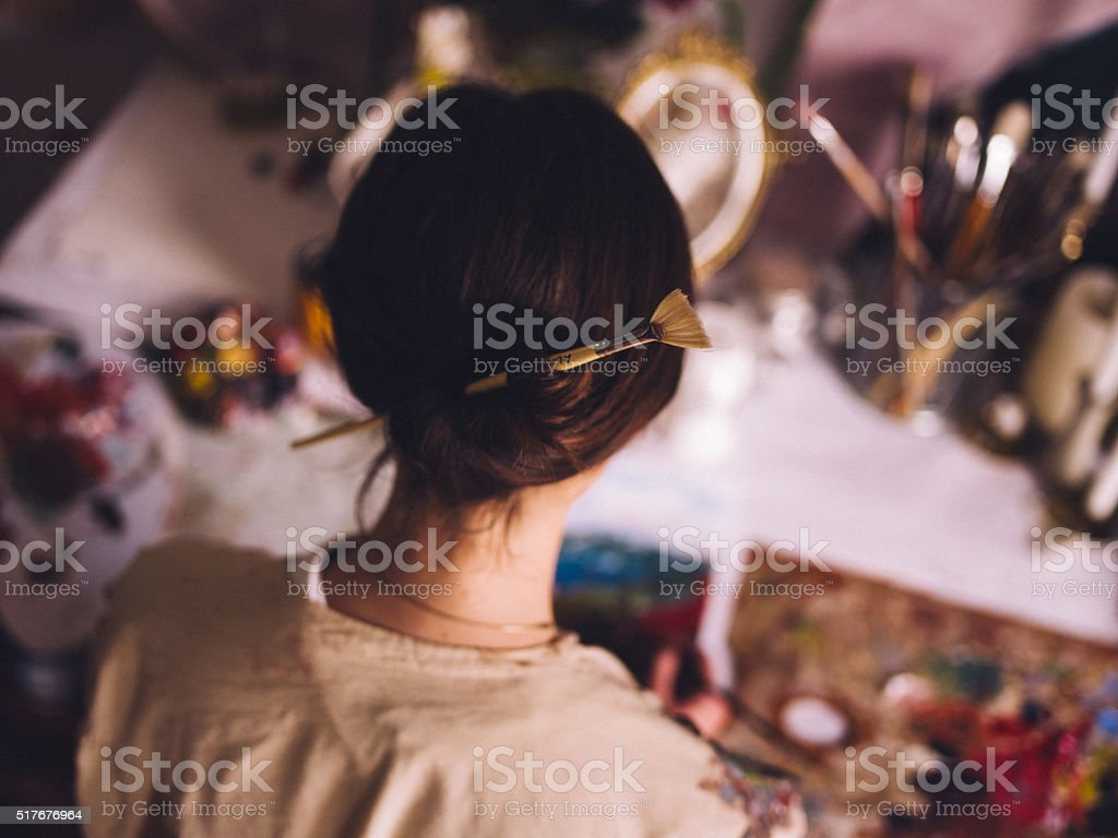 Woman artist working at her studio desk painting stock photo