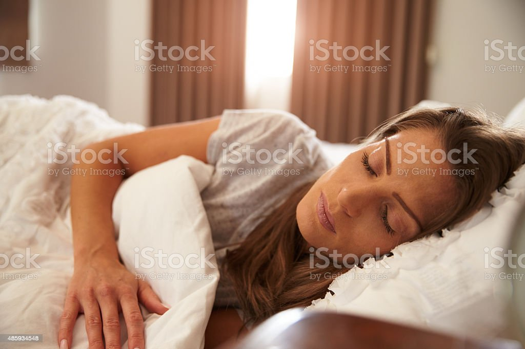 Woman Asleep In Bed As Sunlight Comes Through Curtains stock photo