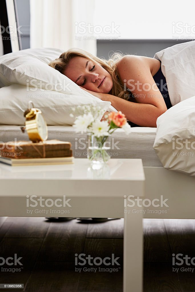 Woman asleep in bed stock photo