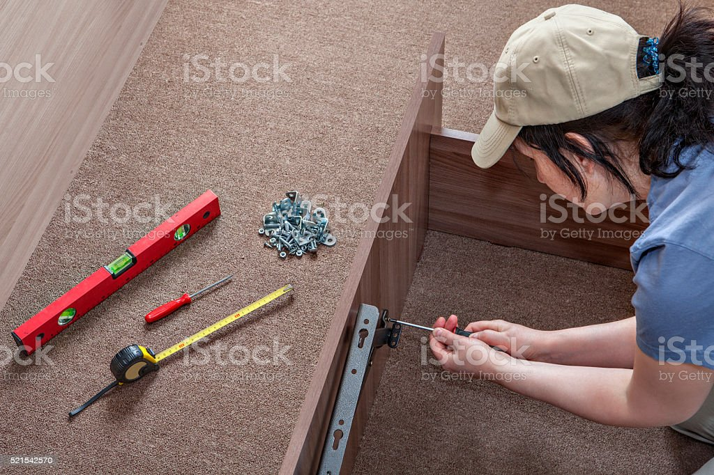 Woman assembles furniture, hinges lifting mechanism screwed to bed frame. stock photo