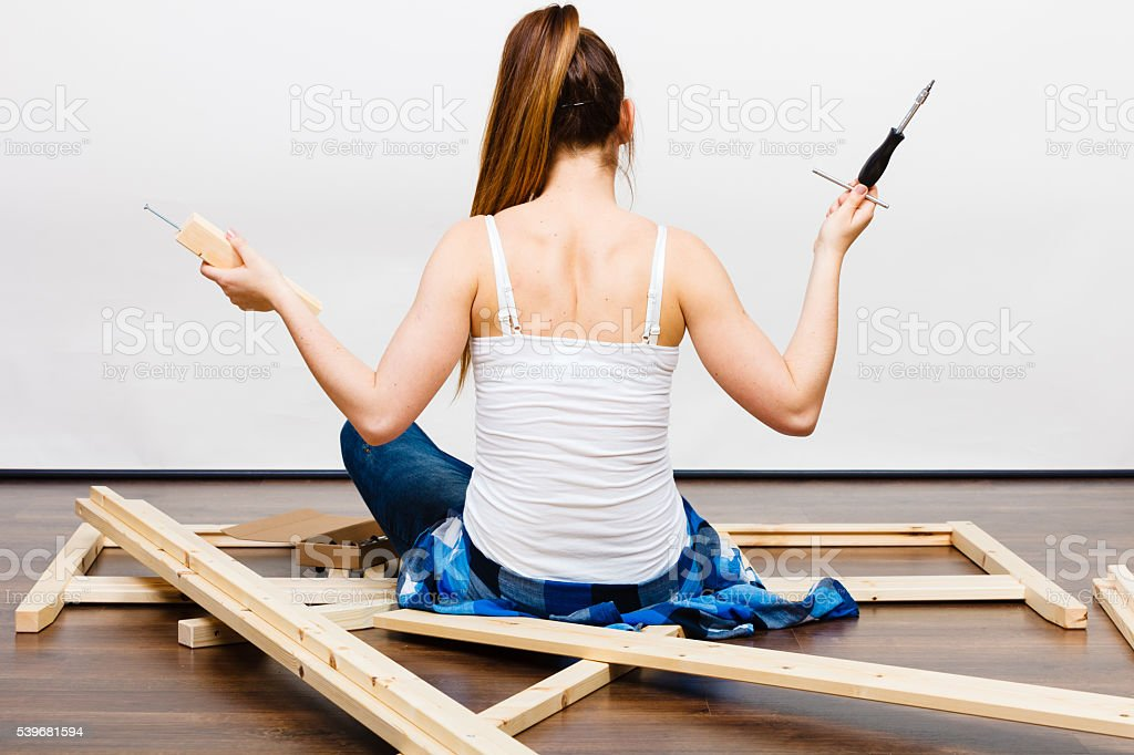 Woman assembling wooden furniture. DIY. Rear view. stock photo