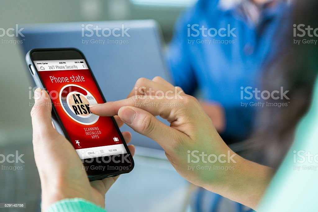 Woman assesses security risk on smart phone stock photo