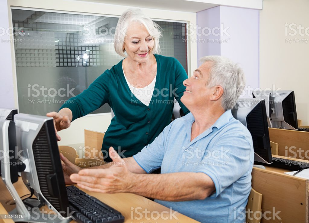 Woman Assisting Classmate In Using Computer At Classroom stock photo