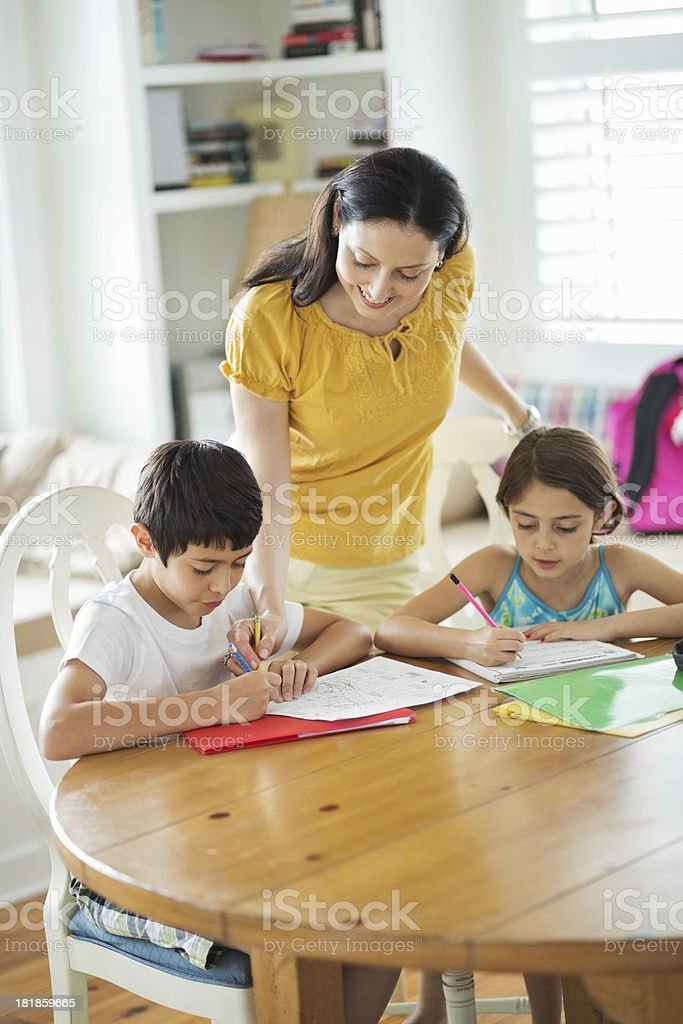 Woman Assisting Son And Daughter With Studies royalty-free stock photo