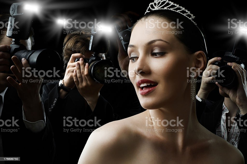 Woman at a black tie event, with paparazzi taking pictures stock photo