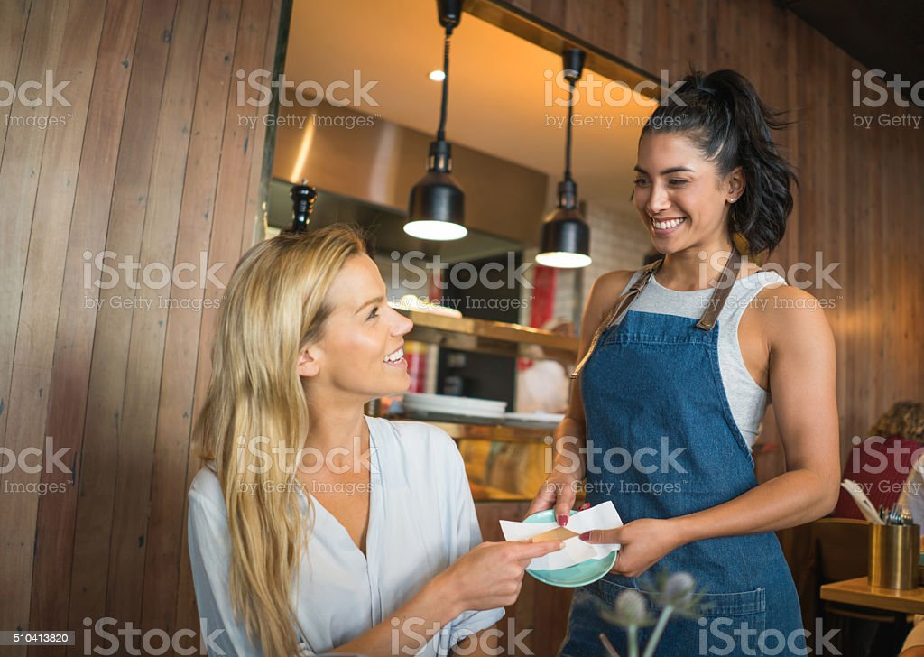 Woman at a cafe paying by card stock photo