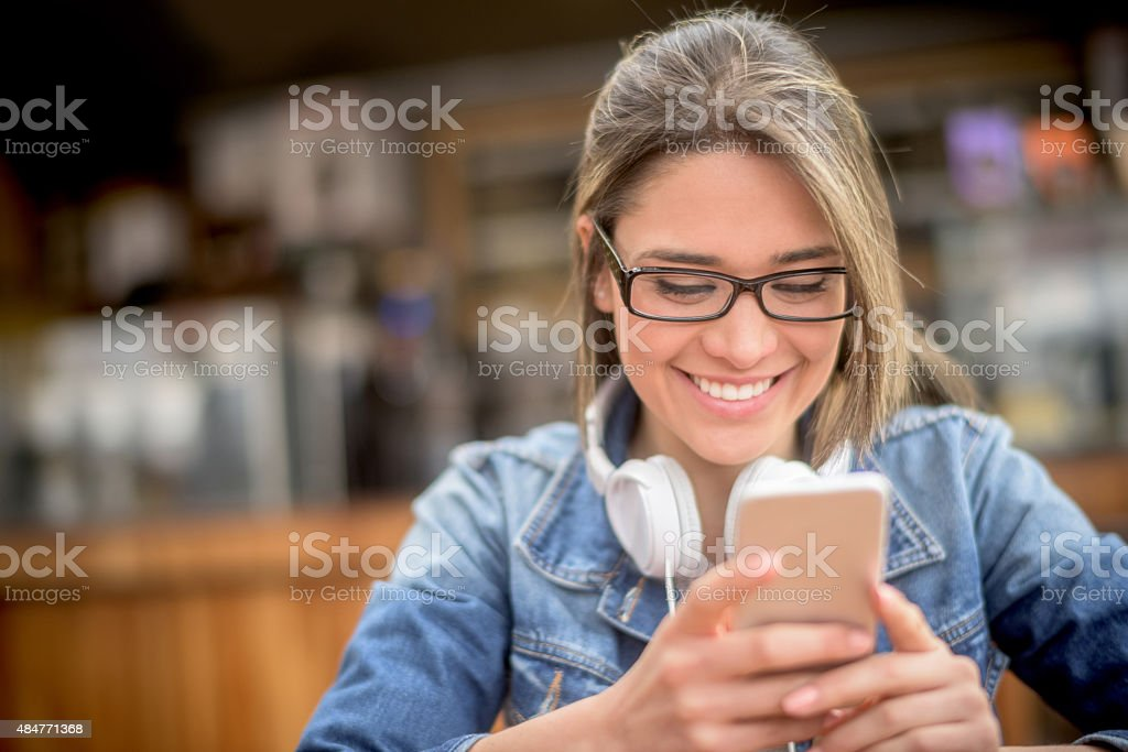 Woman at a coffee shop texting on her phone stock photo