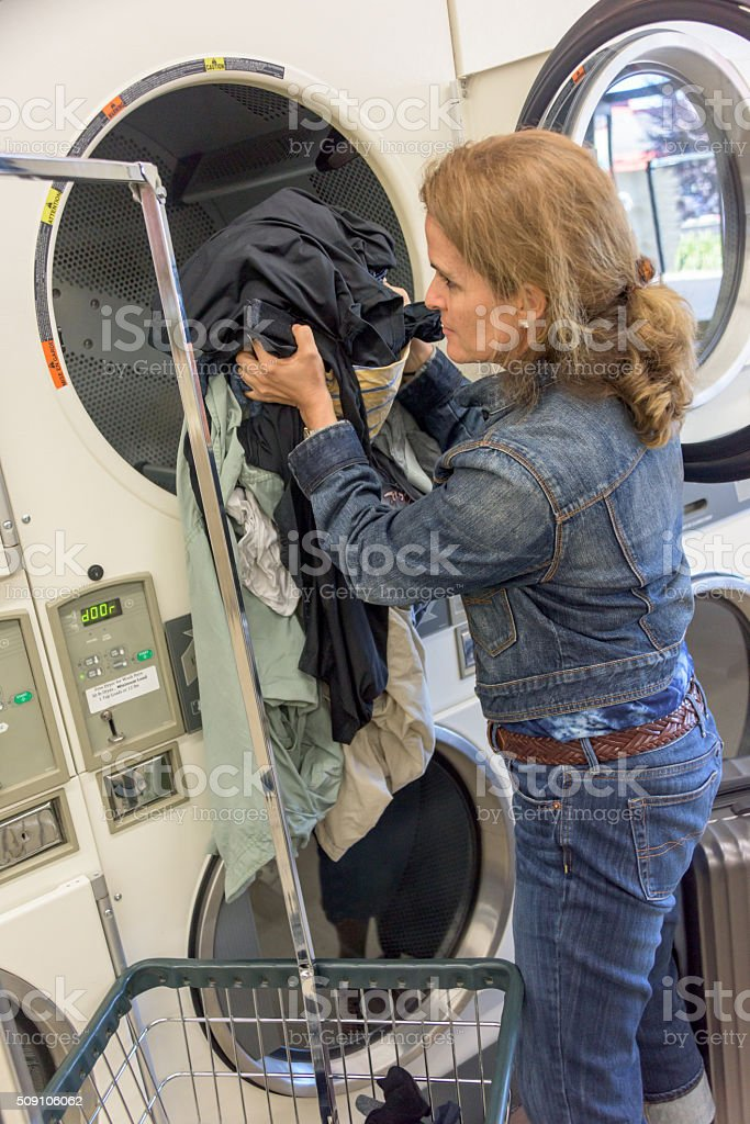 Woman at a coin laundry stock photo