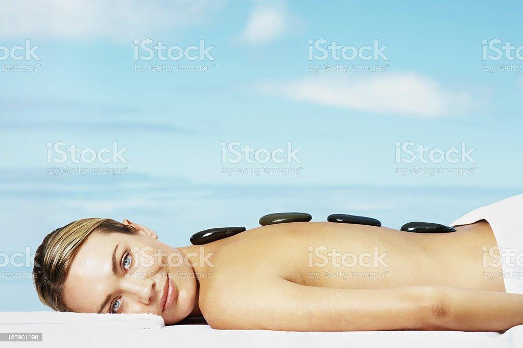 Woman at a day spa having hot stones massage royalty-free stock photo