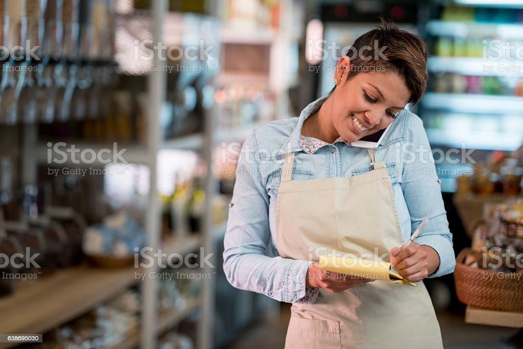 Woman at a grocery store talking on the phone stock photo