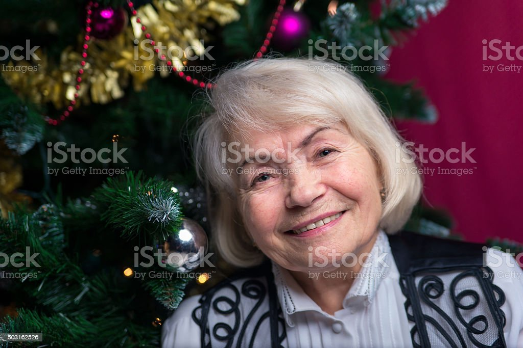 Woman at a mature age against the Christmas tree stock photo