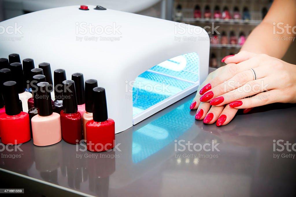 Manicure set in a beauty salon. Beautiful female hands. Machine for...