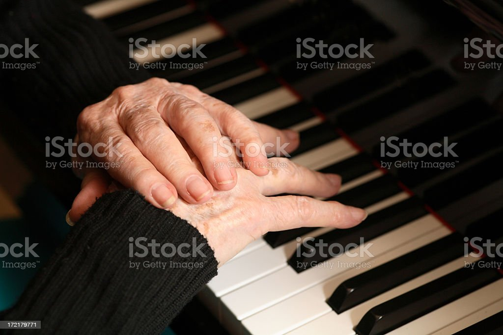 Woman at a piano rubbing her pained hands royalty-free stock photo
