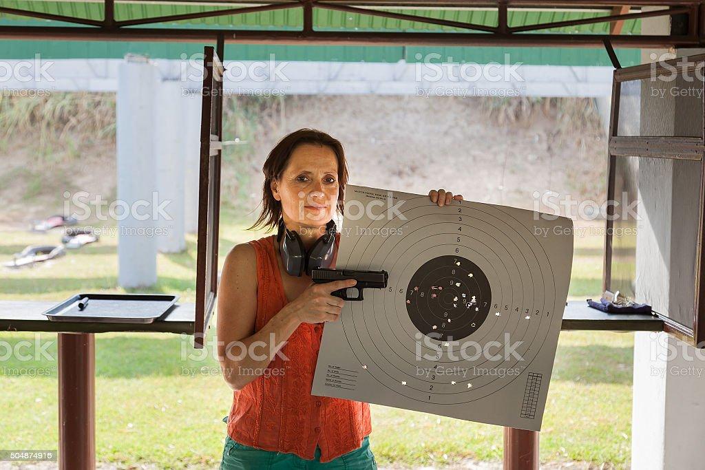 Woman at a shooting range with gun and target stock photo