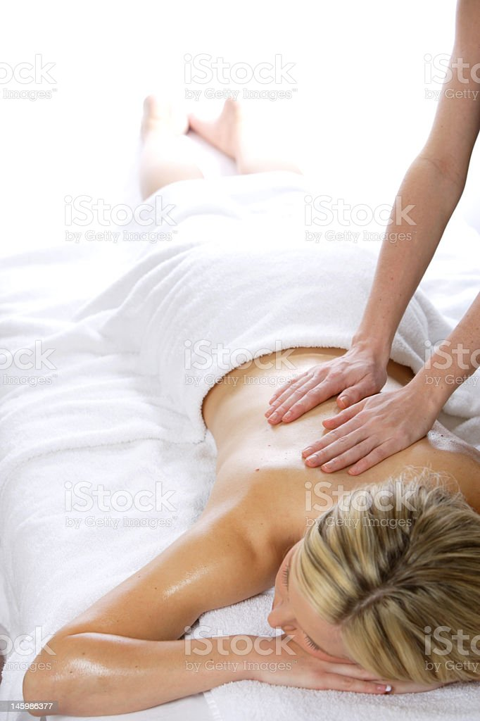 A woman at a spa receiving a massage royalty-free stock photo