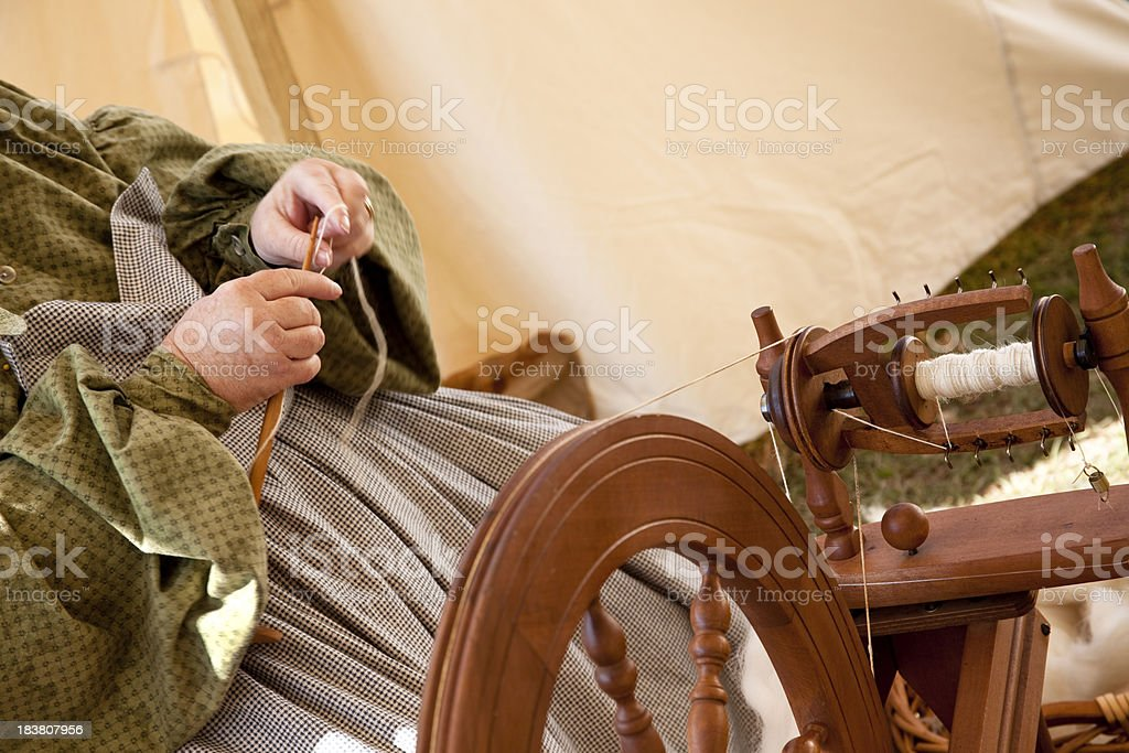 Woman at a spinning wheel, knitting. stock photo