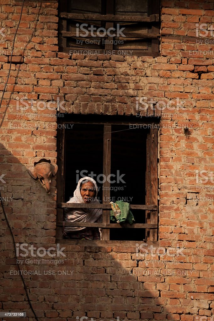 Woman at a window in bhaktapur, Kathmandu, Nepal. stock photo