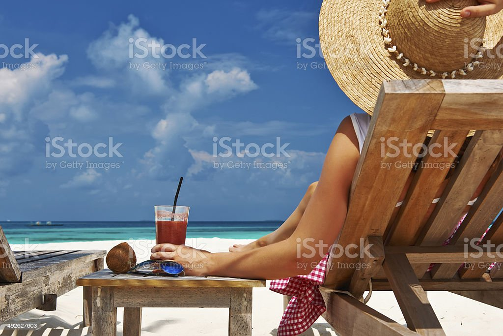Woman at beach with chaise-lounges royalty-free stock photo