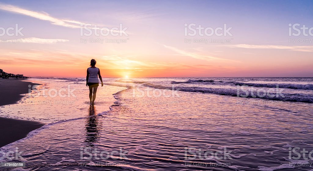 Greeting the morning sun at the beach. stock photo