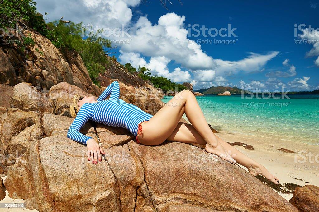 Woman at beautiful beach wearing rash guard stock photo