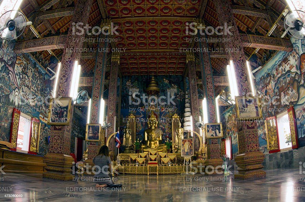Woman praying at Buddhist temple stock photo
