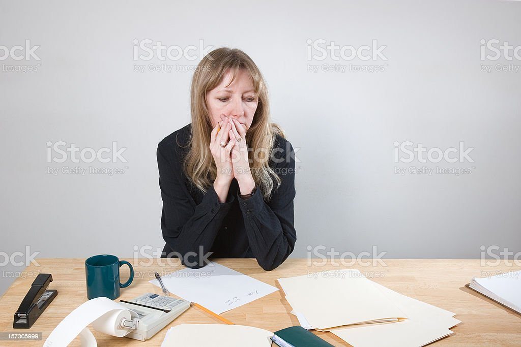 Woman at Desk Worried about Economy and Personal Finances royalty-free stock photo