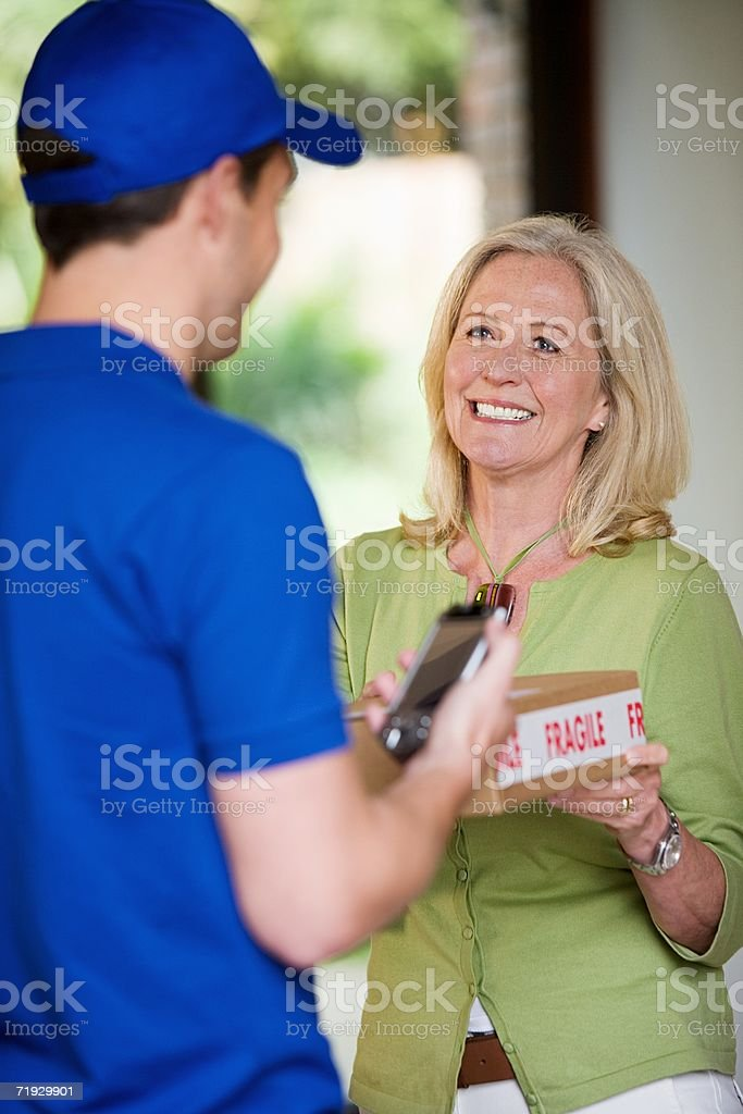 Woman at door with delivery man stock photo