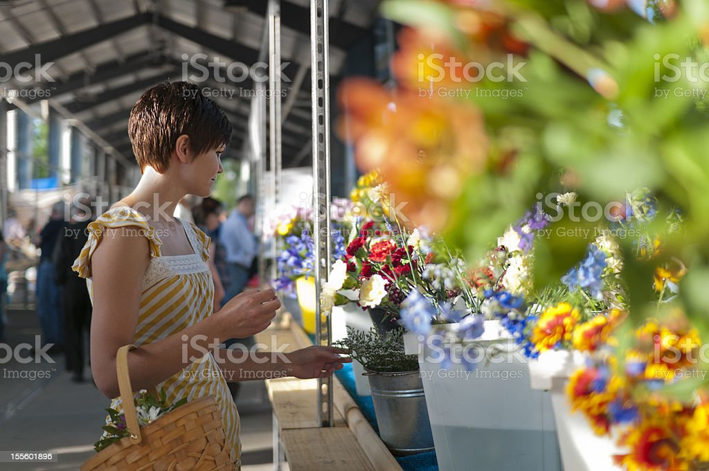 Woman at farmers market with flowers stock photo