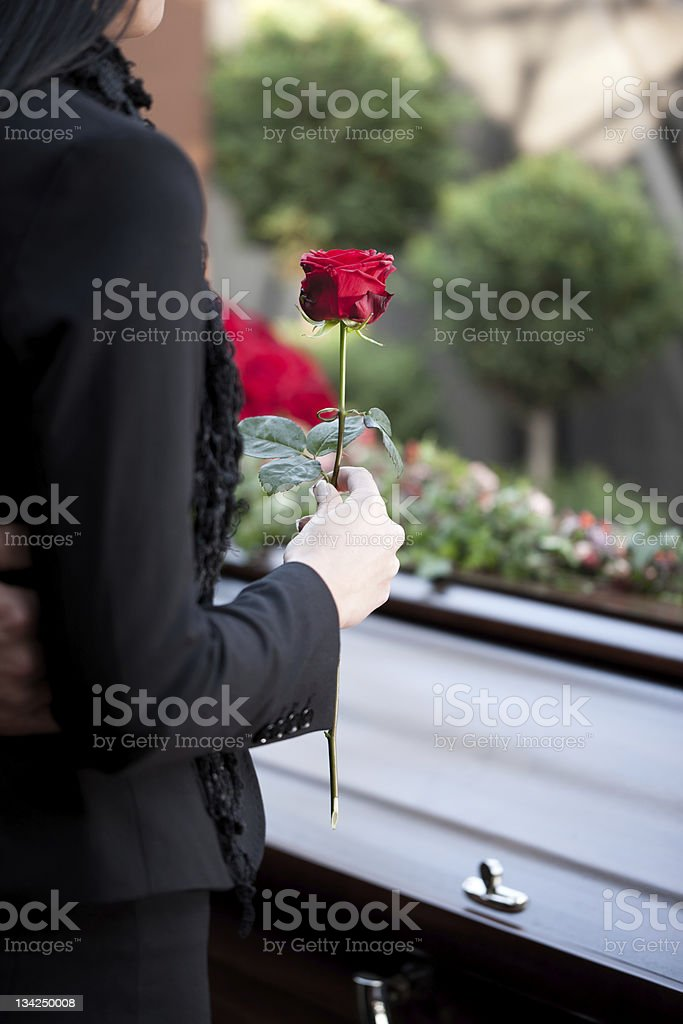 Woman at Funeral with coffin stock photo