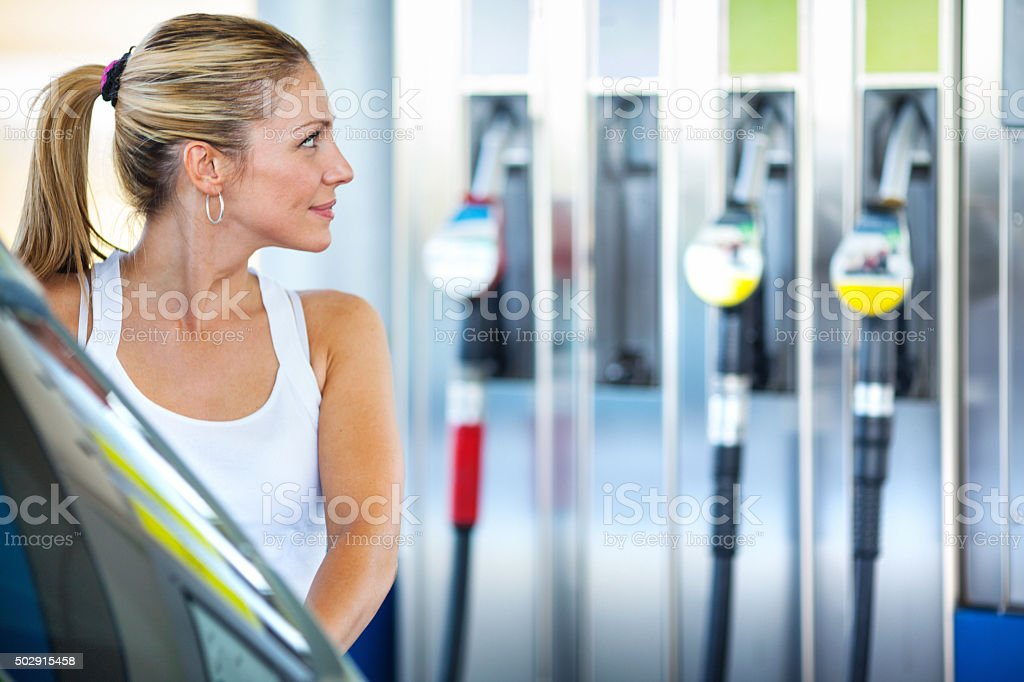 Woman at gas station. stock photo
