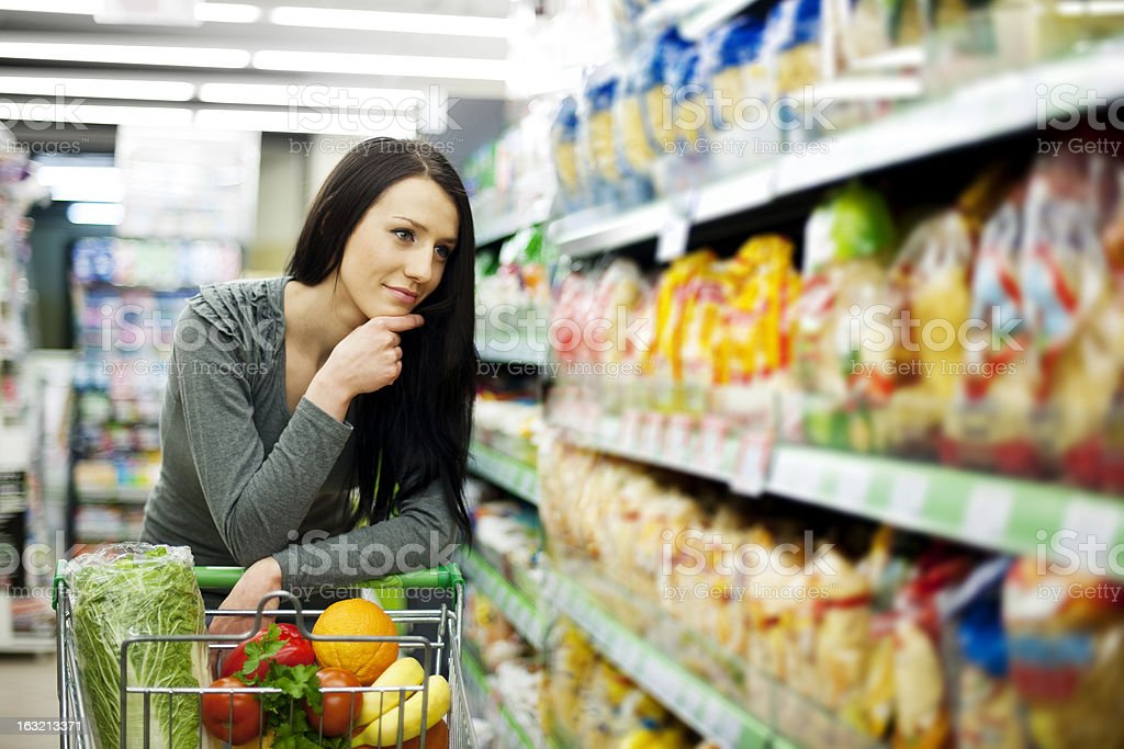 Woman at grocery store looking stock photo